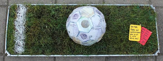 Konfirmationsgave fodbold med pengesedler på rullegræs