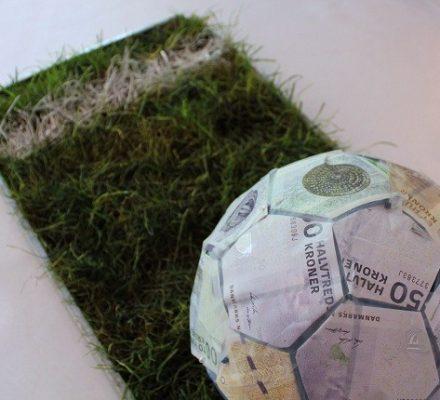 Konfirmationsgave fodbold med pengesedler på rullrgræs