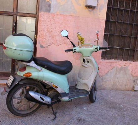 mintfarvet scooter i Italien op af laksefarvet mur