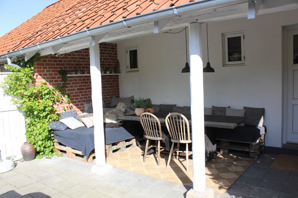 terrasse med bænk og seng af paller