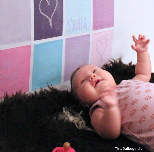 Tavlemaling og tavlelak malet i felter på væggen med hvid, lilla, turkis og pink - blandet til pastelfarvet maling