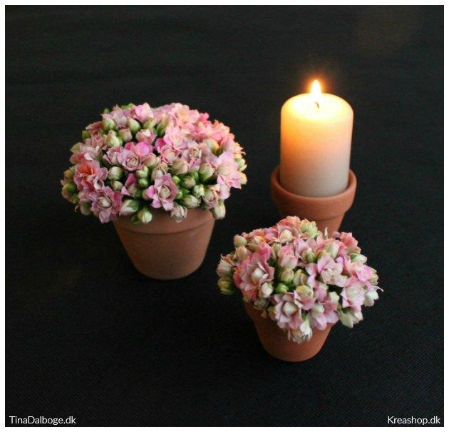 borddækning med blomster og lys i små urtepotter